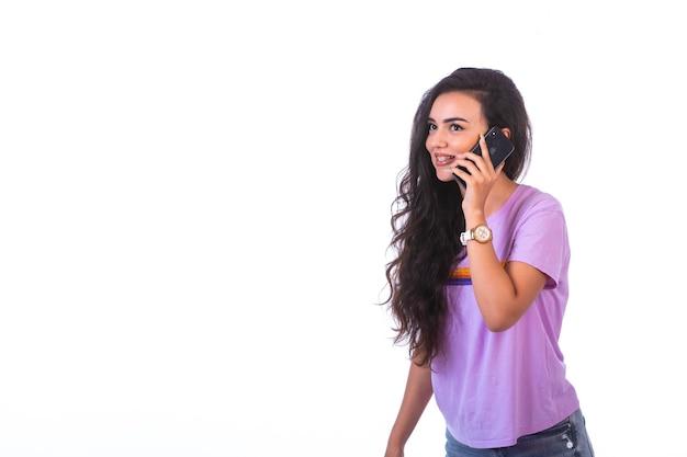 Ragazza giovane avente una telefonata e parlando con uno smartphone nero.
