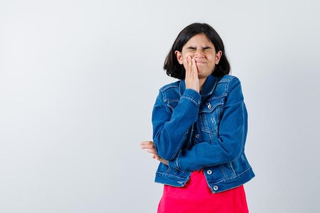 赤いtシャツとジージャンで歯痛があり、疲れ果てているように見える少女。正面図。