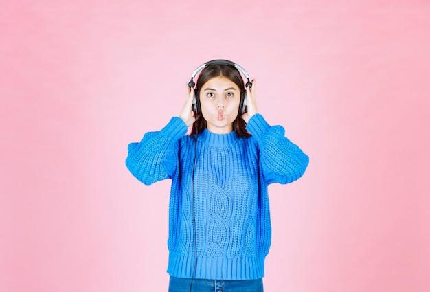 Giovane ragazza in cuffie in piedi sul rosa.