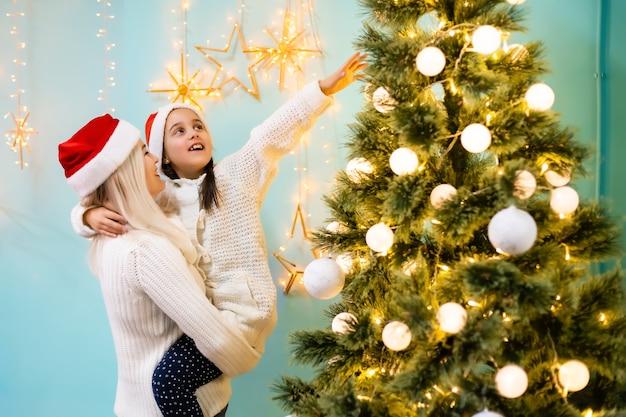 Молодая девушка помогает своей матери украшать елку, держа в руке рождественские шары