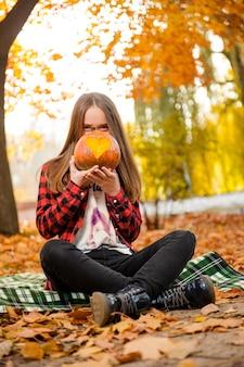 A young girl hiding her face behind a pumpkin