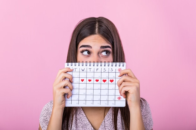 Young girl in hiding behind a menstrual periods calendar and looking away
