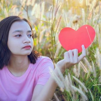 若い女の子は牧草地のアジアの女の子で赤いハート紙を保持します