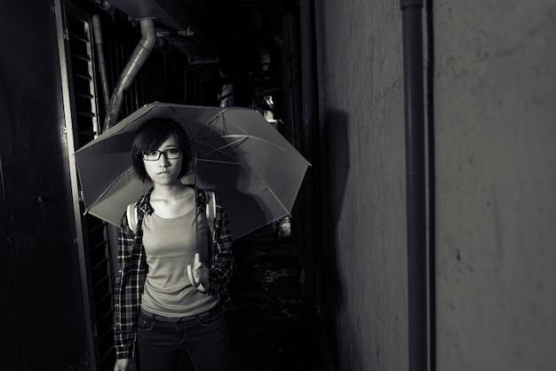 若い女の子は傘を持って、台湾の台北で顔に青い表情で狭い車線に立っています。