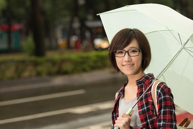 若い女の子は傘を持って、台湾の台北の路上に立っています。