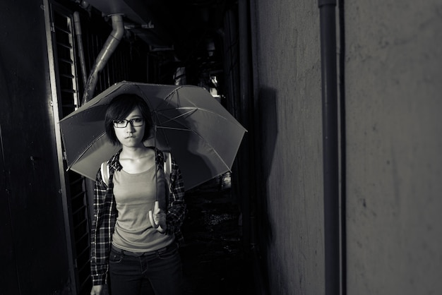 Young girl hold umbrella and stand at narrow lane with blue expression on face in taipei, taiwan.