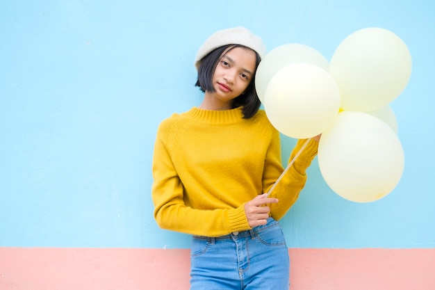 Young girl hold yellow balloon wear yellow sweater smile over blue background.