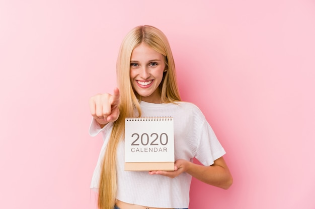 Young girl holding a 2020 calendar cheerful smiles pointing to front.