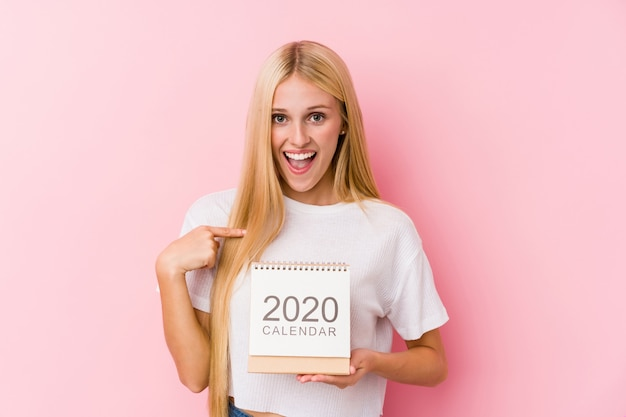Young girl holding a 2020 calendar surprised pointing at himself, smiling broadly