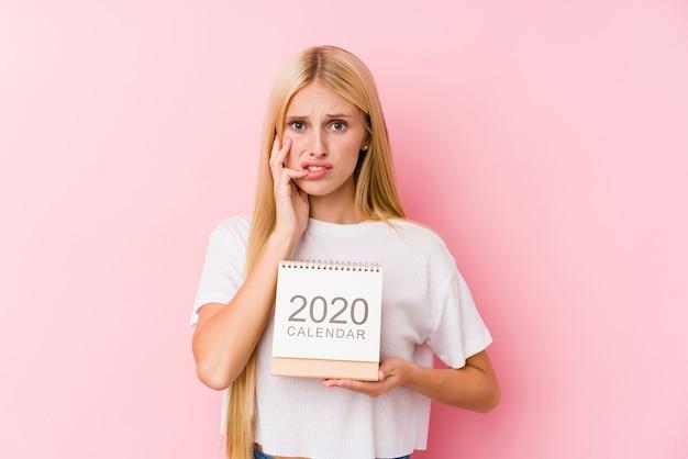 Молодая девушка держит календарь на 2020 год, кусая ногти, нервная и очень взволнованная.