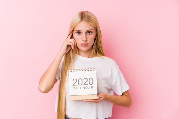 Молодая девушка держит календарь на 2020 год, указывая пальцем на висок