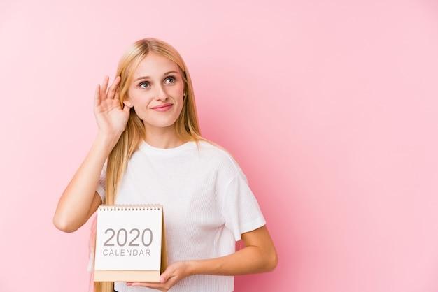 Молодая девушка с календарем на 2020 год пытается слушать сплетню.