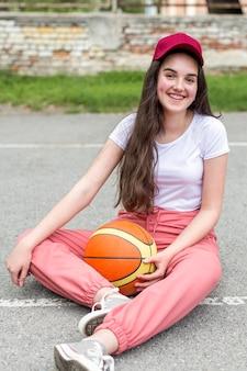 Молодая девушка держит баскетбол сидя
