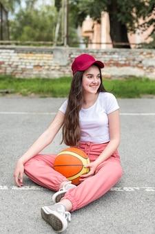 Молодая девушка держит баскетбол