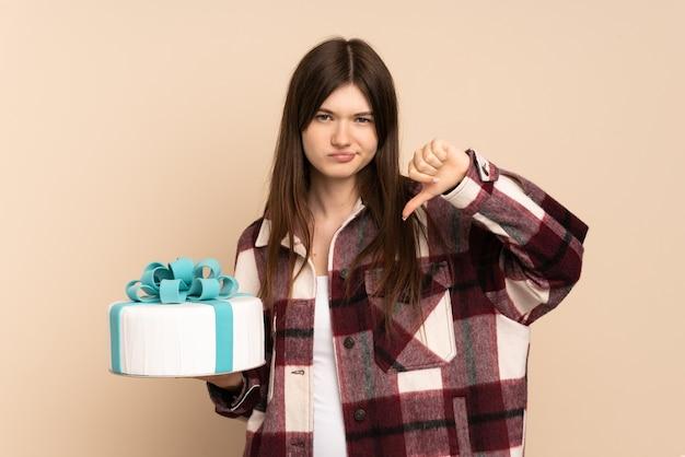 Молодая девушка держит большой торт на бежевом, показывая большой палец вниз с отрицательным выражением лица
