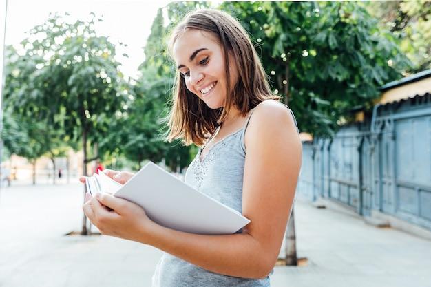 Молодая девушка держит книгу на улице