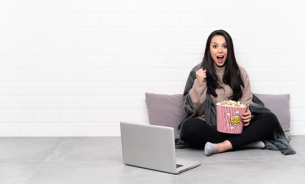 Молодая девушка, держа миску попкорна и показывая фильм в ноутбуке, празднует победу в положении победителя