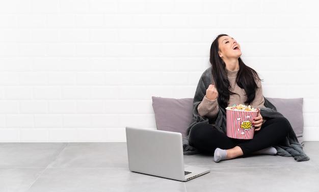 Молодая девушка, держа миску попкорна и показывая фильм в ноутбуке, празднует победу
