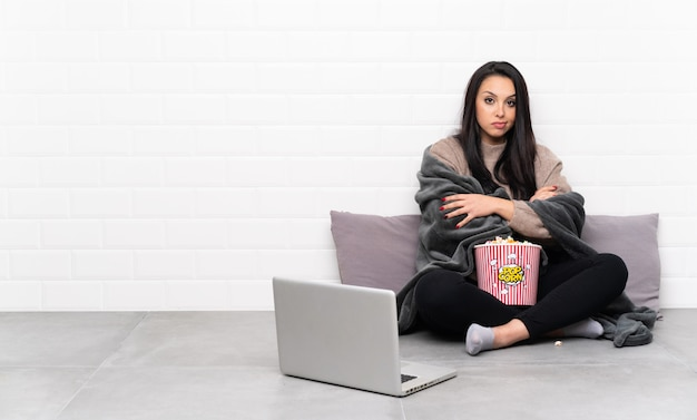 ポップコーンのボウルを押しながら動揺を感じてノートパソコンで映画を見せて若い女の子