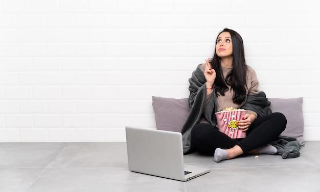 Молодая девушка держит миску попкорна и показывает фильм в ноутбуке, скрестив пальцы и желая лучшего