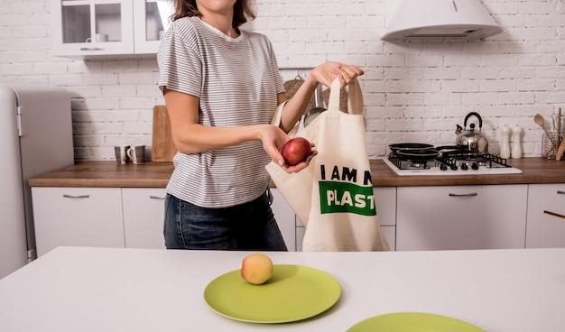 Молодая девушка держит мешок ткани. на кухне. я не пластик.