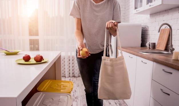 Молодая девушка держит мешок ткани. на кухне.