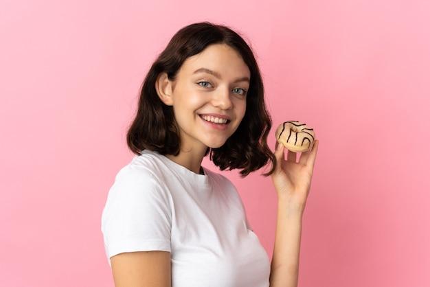 Молодая девушка держит пончик