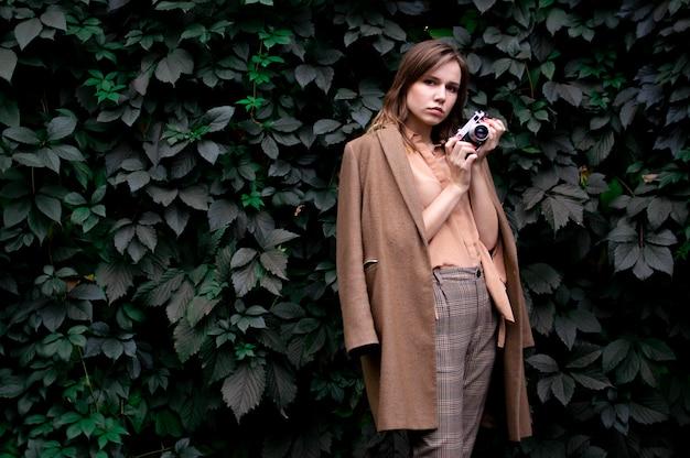 Молодая девушка с пленочной камерой возле стены листьев