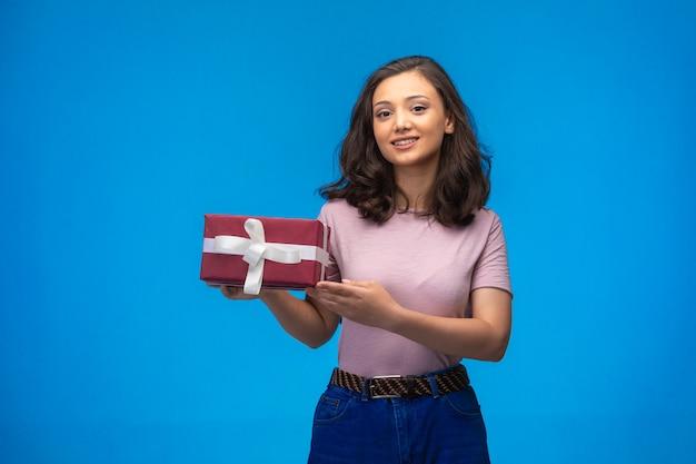 ギフトボックスを保持し、青い背景に笑みを浮かべて若い女の子。