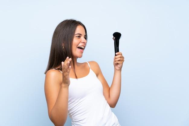 驚きの表情で化粧ブラシの多くを保持している若い女の子