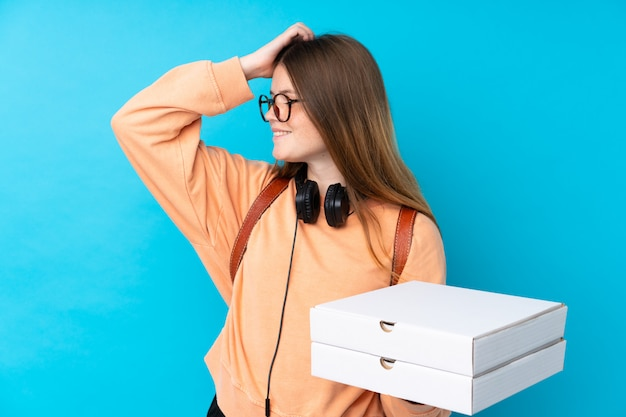 Молодая девушка держит коробки пиццы на синем фоне
