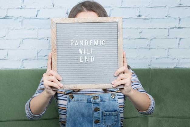 Covidとパンデミックに対してポスターを保持している少女