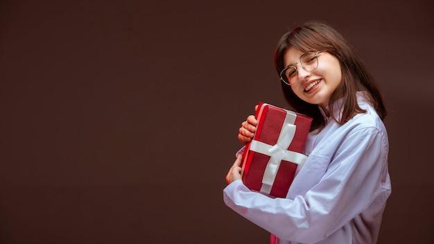 Молодая девушка держит красную подарочную коробку и обнимает ее.