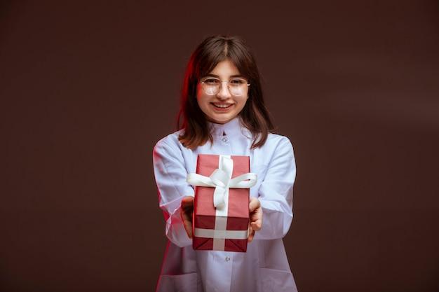 赤いギフトボックスを保持している少女。