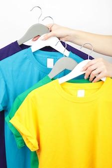 カラフルなtシャツのセットを保持している若い女の子