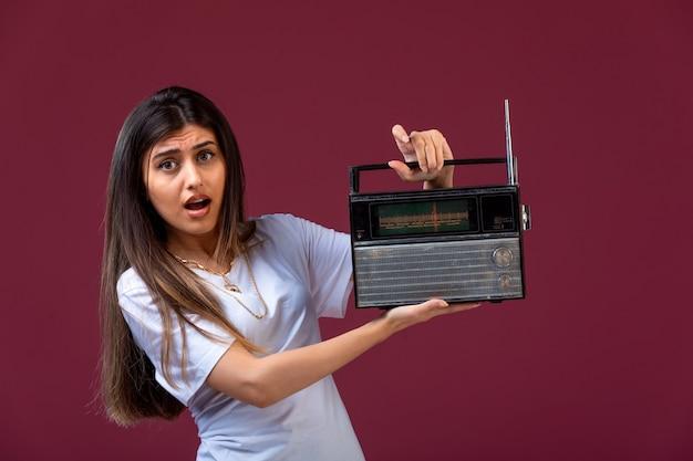 Молодая девушка держит в руке старинное радио и выглядит удивленным