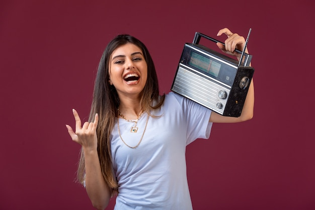 Молодая девушка держит старинное радио на плече и веселится