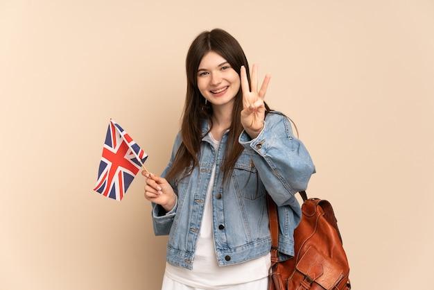 Молодая девушка держит флаг соединенного королевства изолирована на бежевом счастливом и считает три пальцами
