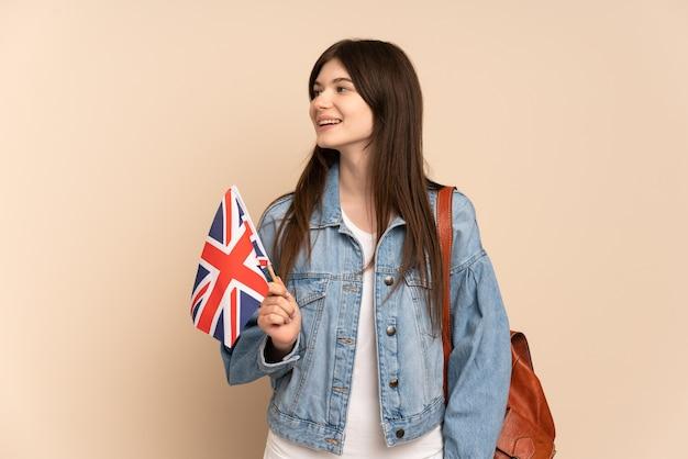 Молодая девушка держит флаг соединенного королевства, изолированный на бежевом, глядя в сторону
