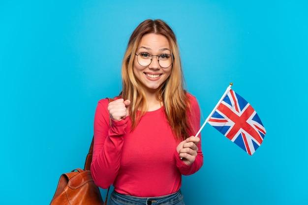 Молодая девушка держит флаг соединенного королевства на изолированном синем фоне, празднует победу в позиции победителя