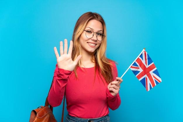 Молодая девушка держит флаг соединенного королевства на изолированном синем фоне, считая пять пальцами