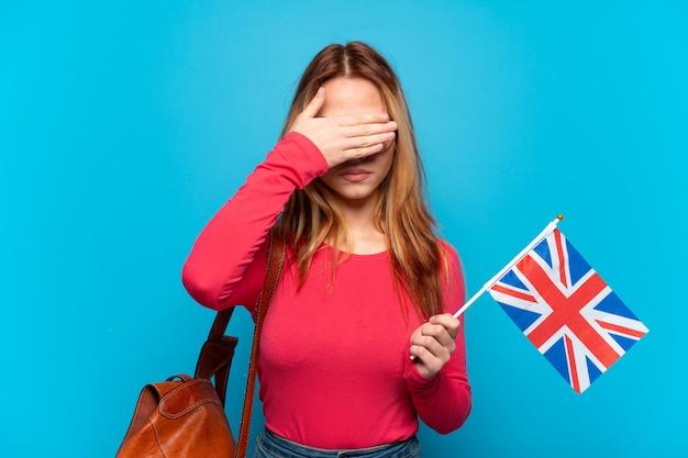 Молодая девушка держит флаг соединенного королевства на изолированном синем фоне, закрывая глаза руками. не хочу что-то видеть