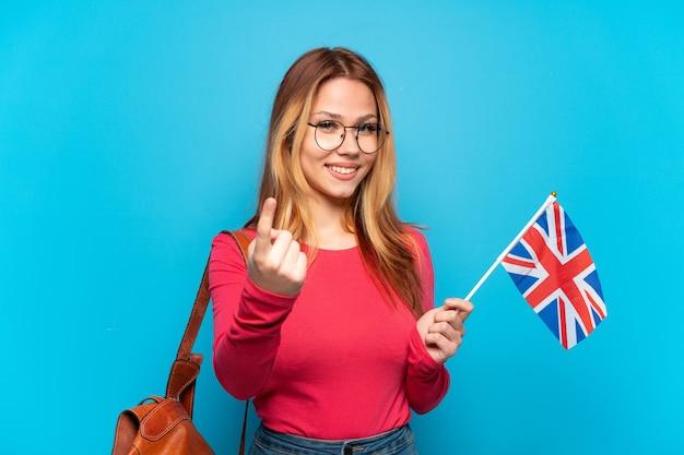 Молодая девушка держит флаг соединенного королевства на изолированном синем фоне, делая приближающийся жест