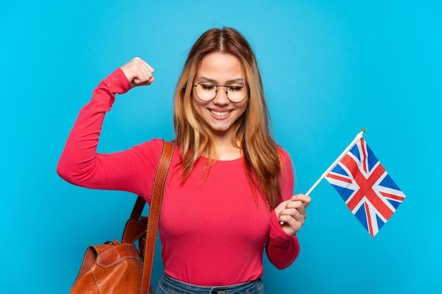 Молодая девушка держит флаг соединенного королевства на изолированном синем фоне, делая сильный жест