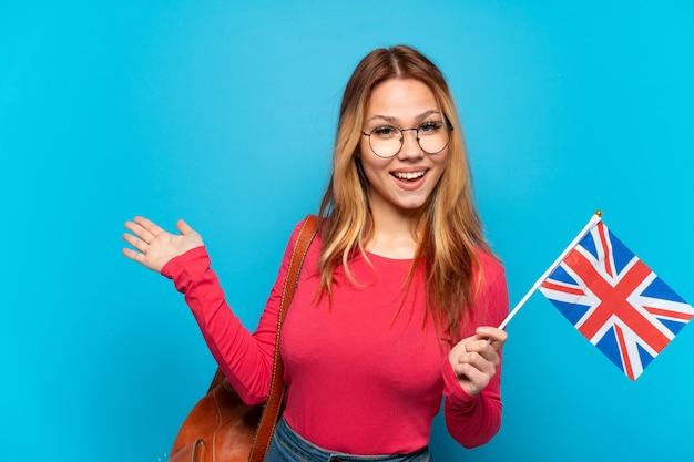 孤立した青い背景の上にイギリスの旗を持って来るように招待するために手を横に伸ばしている若い女の子