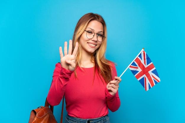 Молодая девушка держит флаг соединенного королевства на изолированном синем фоне счастлива и считает четыре пальцами
