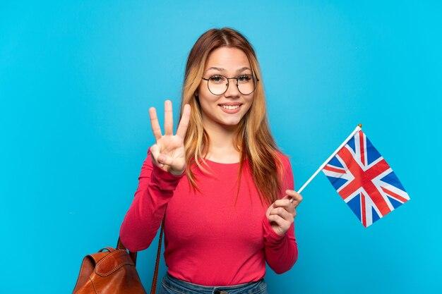 幸せな孤立した青い背景の上にイギリスの旗を保持し、指で3を数える少女