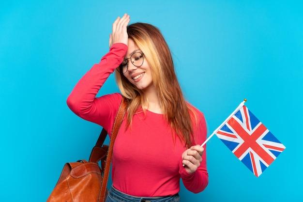 격리 된 파란색 배경 위에 영국 국기를 들고 어린 소녀는 뭔가를 실현하고 해결책을 계획하고 있습니다