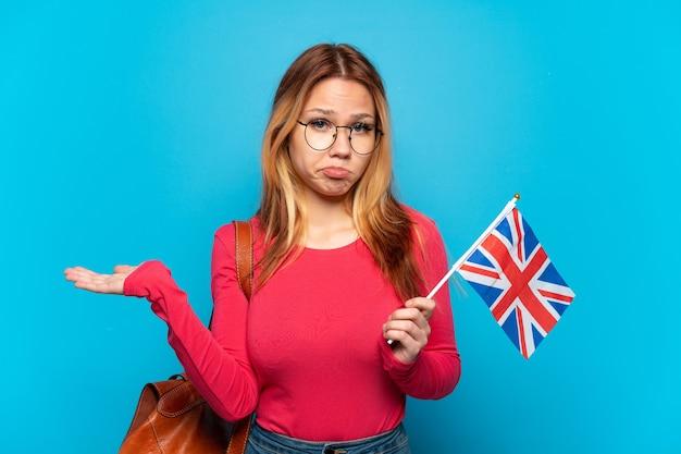 손을 올리는 동안 의심을 갖는 고립 된 파란색 배경 위에 영국 국기를 들고 어린 소녀