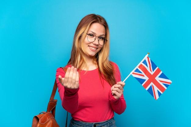 手で来るように誘う孤立した青い背景の上にイギリスの旗を保持している若い女の子。あなたが来て幸せ